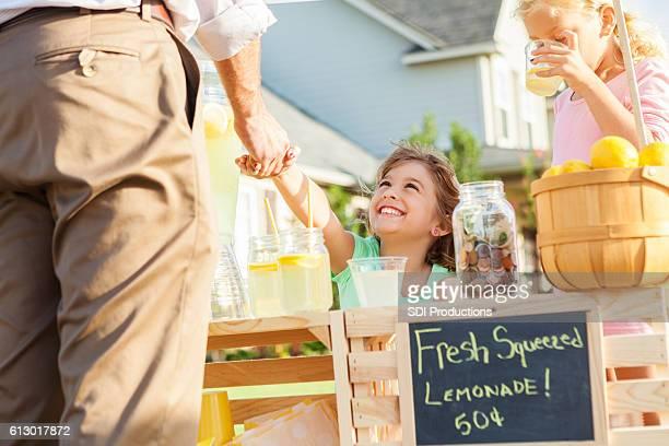 Happy girl sells lemonade to a customer
