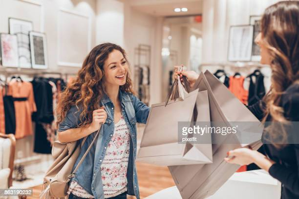 happy girl shopping in the fashion store - shopping bag stock pictures, royalty-free photos & images