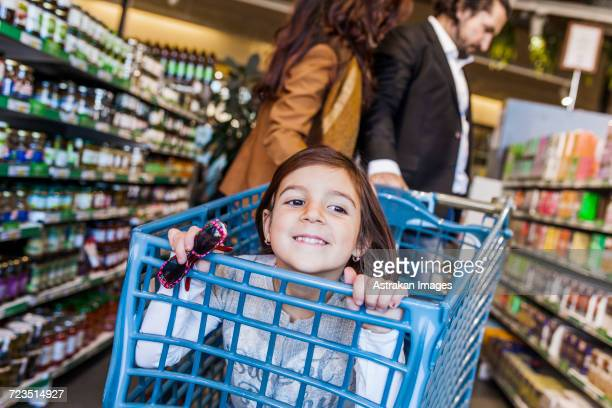 Happy girl sitting in cart with parents at supermarket