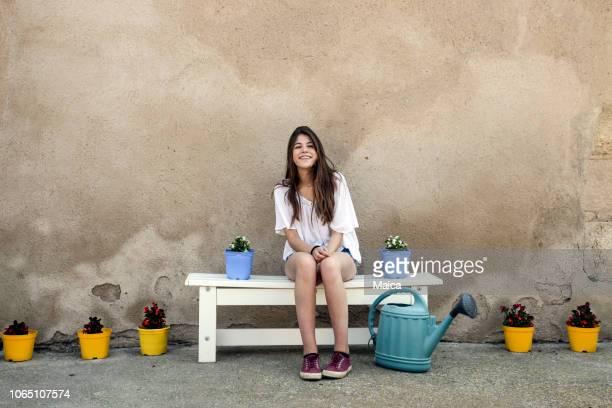 glückliches mädchen sitzen auf einer terrasse-bank - mädchen 14 jahre stock-fotos und bilder