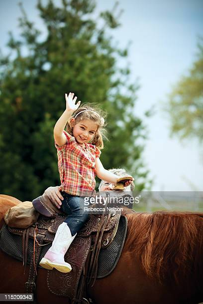 Happy girl sitting on saddled horse