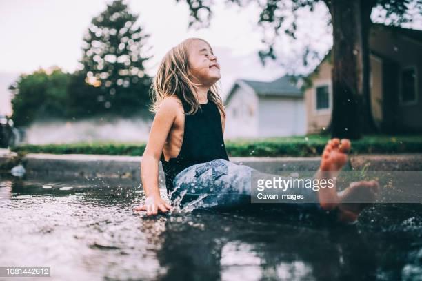 happy girl sitting on wet street during rainy season - extremwetter stock-fotos und bilder