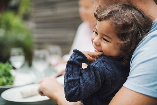 happy girl sitting with father having food at outdoor table - biting nails in kids stock pictures, royalty-free photos & images