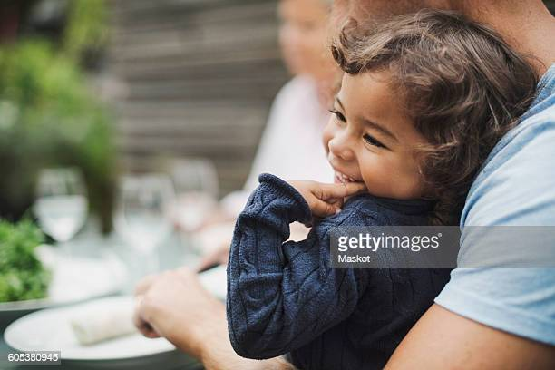 Happy girl sitting with father having food at outdoor table