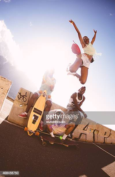 Happy girl skater jumping over friends with joy