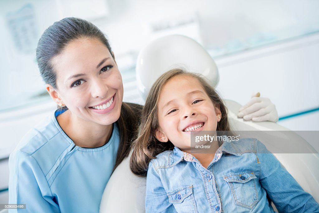 Happy girl smiling at the dentist : Stock Photo
