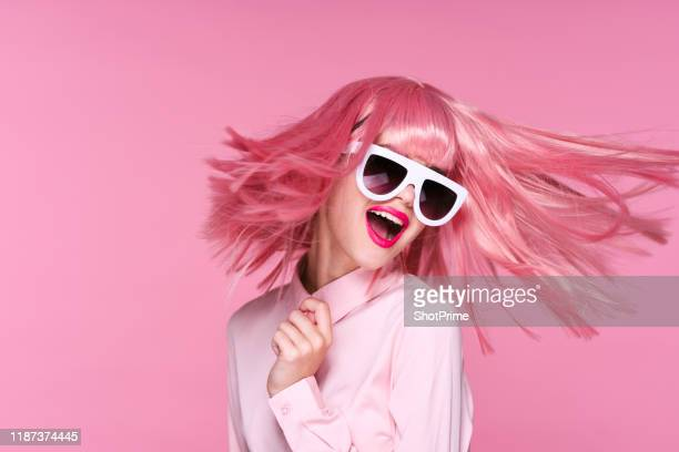 happy girl smiling beautifully on pink background with flying pink hair in white glasses - flying solo after party bildbanksfoton och bilder