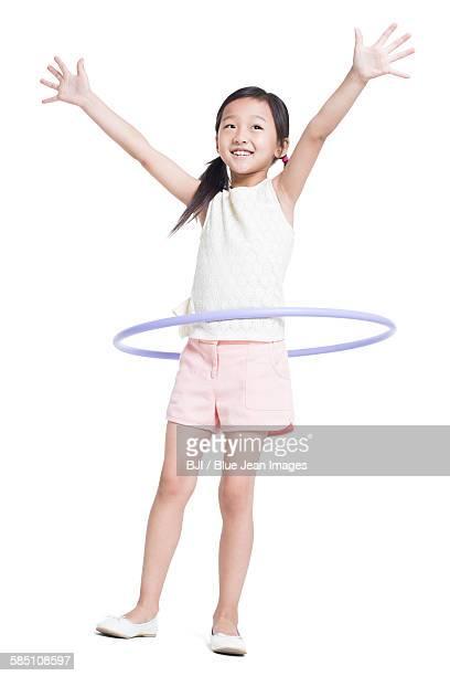 Happy girl spinning plastic hoop