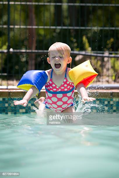 happy girl splashes as she jumps into the swimming pool - arm band stock pictures, royalty-free photos & images