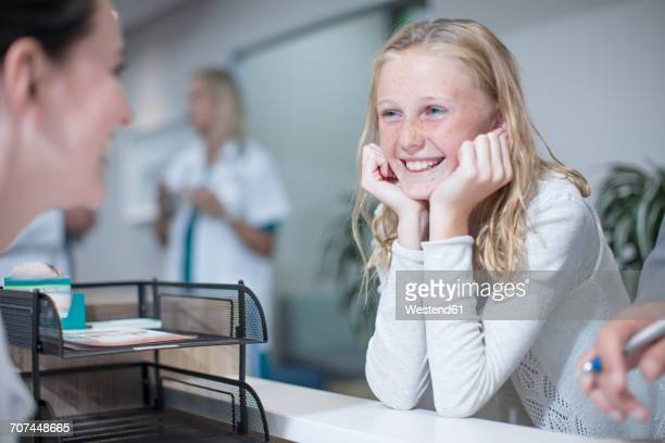 Happy girl standing at hospital reception