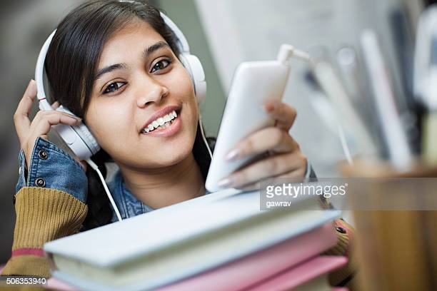 Happy girl student listening music through headphones and smartphone.