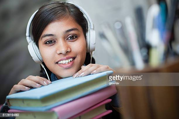 Happy girl student listening music through headphones on study table.