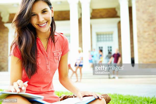 Happy girl studying in campus park