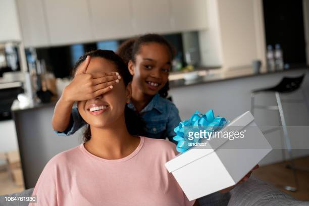 happy girl surprising her mother with a gift for mother's day - black mothers day stock pictures, royalty-free photos & images