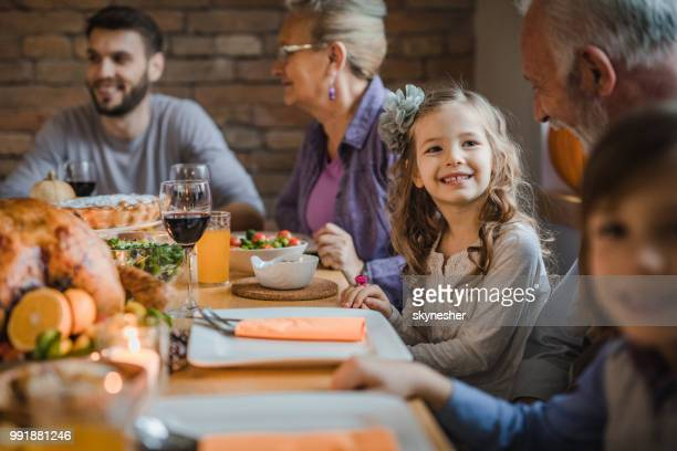 happy girl talking to her grandfather during dinner at dining table. - evening meal stock pictures, royalty-free photos & images