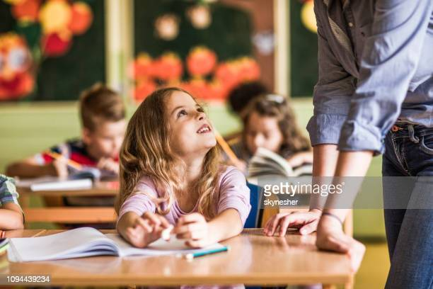 happy girl talking to her unrecognizable teacher on a class in elementary school. - elementary age stock pictures, royalty-free photos & images