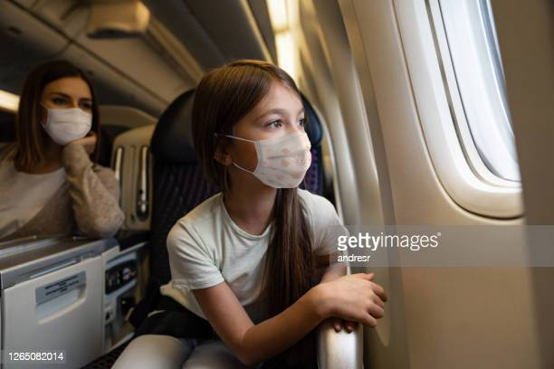 happy girl traveling by plane wearing a facemask - kid in airport stock pictures, royalty-free photos & images