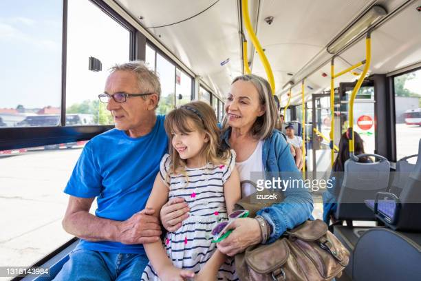 happy girl traveling with grandparents in bus - izusek stock pictures, royalty-free photos & images