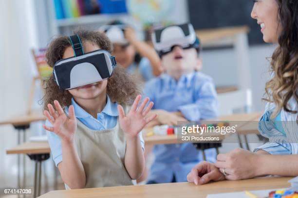 Glückliches Mädchen nutzt virtual-Reality-Brille in der Schule
