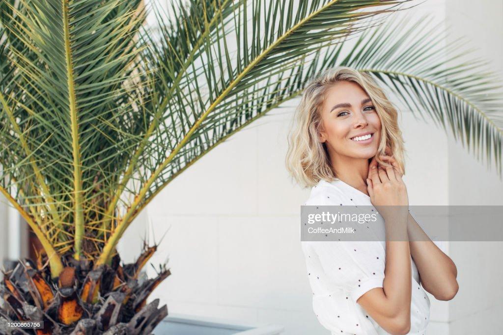 Happy girl walking near palm trees on a summer sunny day : Stock Photo