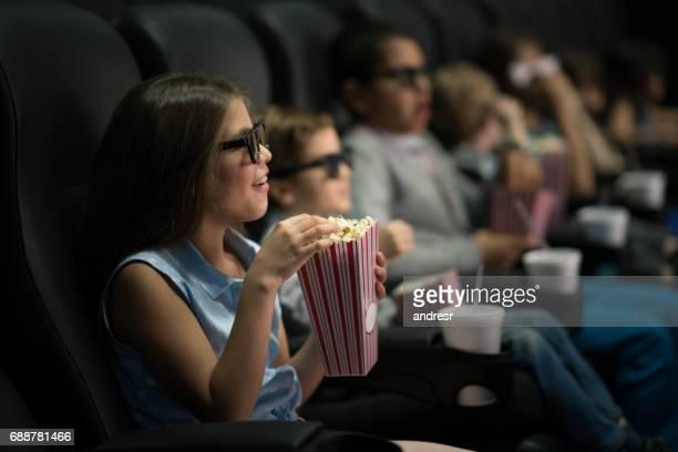 Glückliches Mädchen mit 3D-Brille im Kino mit einer Gruppe von Freunden