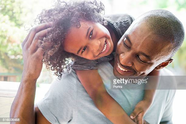 happy girl with arms around father at home - african american family home stock photos and pictures