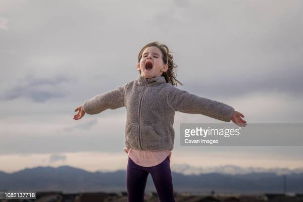 happy girl with arms outstretched screaming while standing against cloudy sky - nur kinder stock-fotos und bilder