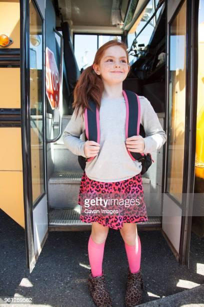 happy girl with backpack at bus doorway - innocence stock pictures, royalty-free photos & images