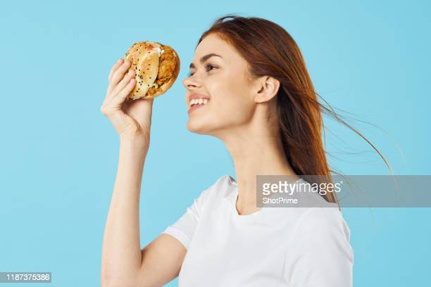 happy girl with burger in hand on blue background - fast fashion stock pictures, royalty-free photos & images