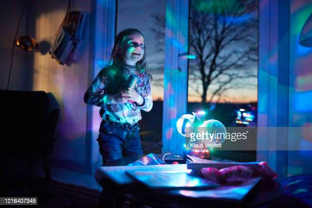 happy girl with microphone singing in living room with disco ball - authenticity stock pictures, royalty-free photos & images