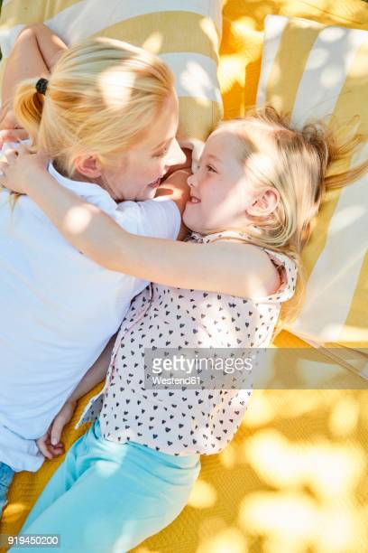 Happy girl with mother lying on a blanket