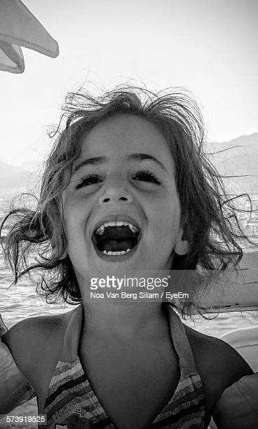 happy girl with mouth open at beach - girls open mouth stock-fotos und bilder