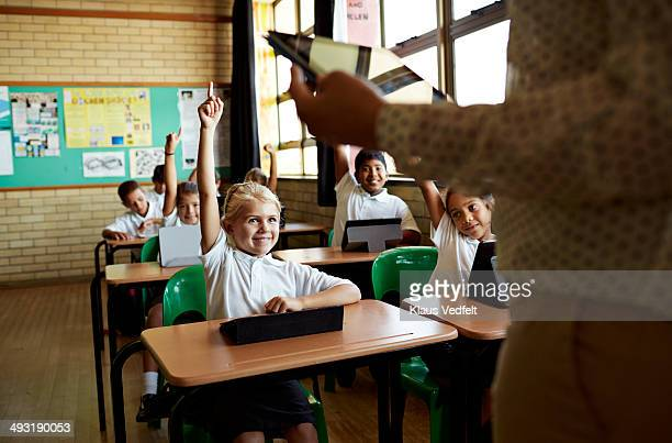 Happy girl with raised hand in class
