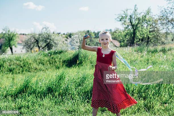 Happy girl with ribbon in meadow