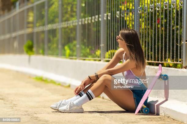 Happy girl with skateboard near wall