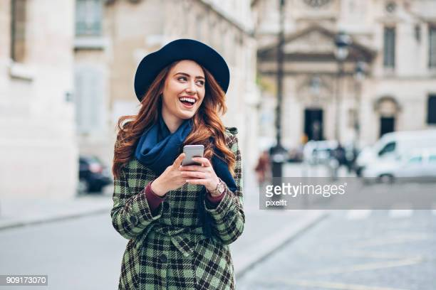 Happy girl with smart phone on the street