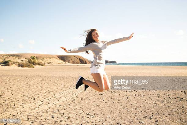 Happy girl with smile jumping on the Lanzarote beach during a travel vacations in a windy day.