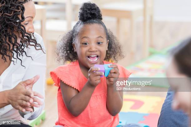 ブロック玩具で遊ぶ特別なニーズを持つ幸せな女の子 - 歯を見せて笑う ストックフォトと画像