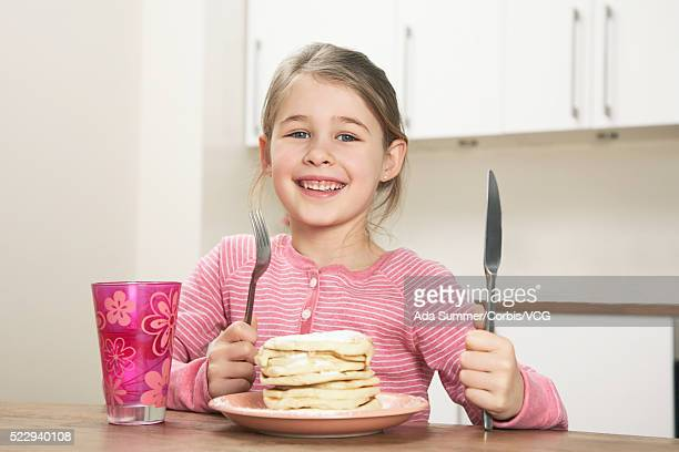Happy girl with stack of pancakes