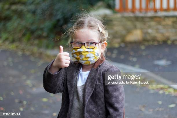 happy girl with thumb up wearing a face mask - girls stock pictures, royalty-free photos & images