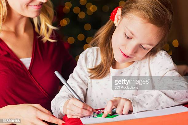 Happy girl writing in a Christmas card with her mom