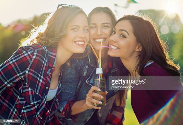 Happy girlfriends are drinking together from the same bottle making fun