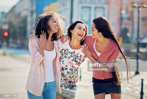 happy girlfriends are hugging and walking together - girlfriend stock pictures, royalty-free photos & images