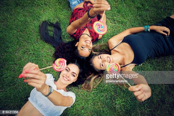 Happy girlfriends are lying down on the grass and playing with a lollipops