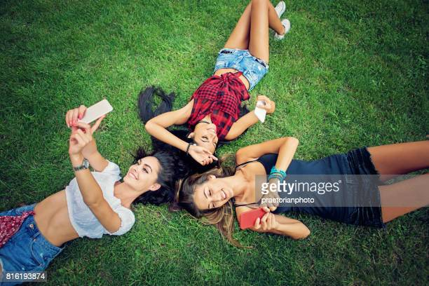 Happy girlfriends are lying down on the grass texting and taking selfie/video call