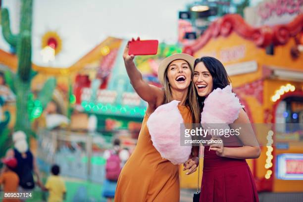 happy girlfriends are taking selfie/making video call and make fun together in fun fair - girlfriend stock pictures, royalty-free photos & images