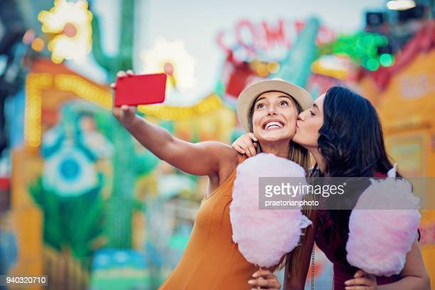 happy girlfriends are taking selfie/making video call and make fun together in a fun fair - cotton candy stock pictures, royalty-free photos & images