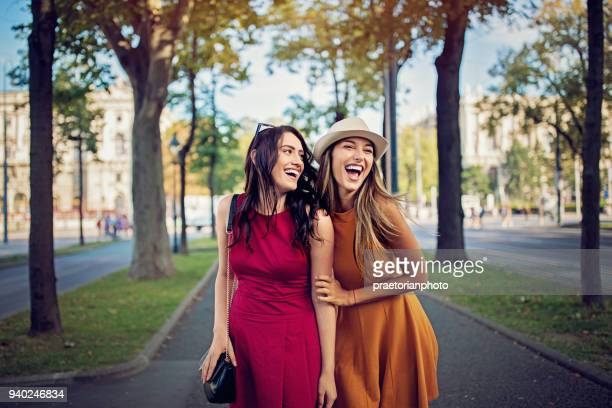 Happy girlfriends are walking and hugging in the city and make fun together
