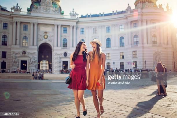Amigas felizes caminan y ríen juntos en el centro de Viena