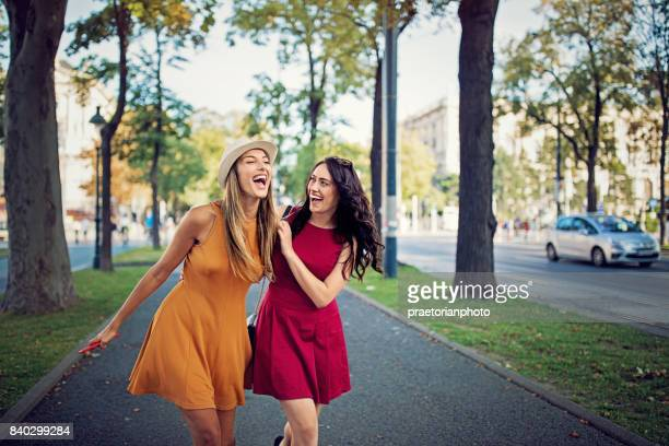 happy girlfriends are walking in the city and make fun together - girlfriend stock pictures, royalty-free photos & images